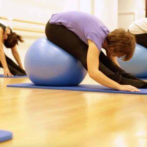 Mujer sentada estirando en una clase de yoga